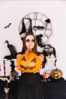Teenage girl with vampire makeup holding pumpkin ahead