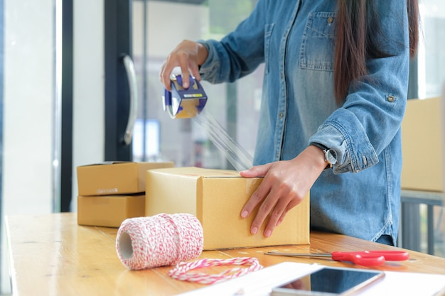 Teenage girls are packing products in boxes and using clear adhesive tape to deliver to customers.