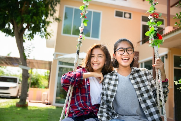Teenage girls enjoy playing swing together, diverse ethnicities
