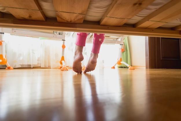 Ноги девочек-подростков под кроватью в солнечное утро
