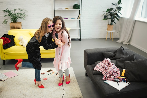 Teenage girls on high heels holding together microphone and sing into it. they wear clothes and shoes for adult women. gils have fun and enjoy.