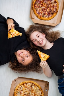 ピザの箱を押しながら笑顔の10代の少女。ピザの配達の概念。
