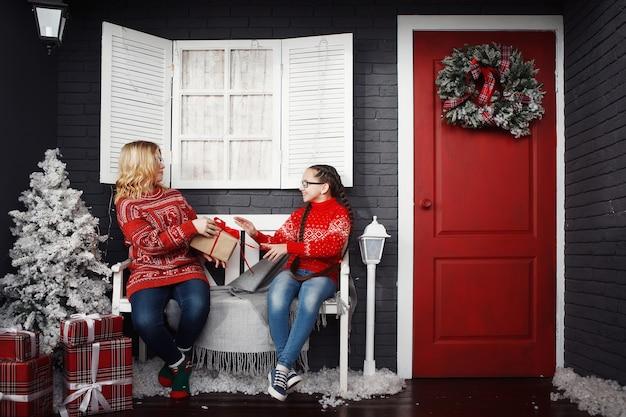 Девочки-подростки в красном рождественском свитере дарят подарочные коробки, сидя на скамейке.