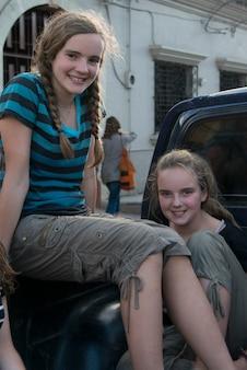 Девочки-подростки на грузовике и улыбаются, баррио-эль-центро, копан, копан-руинас, гондурас