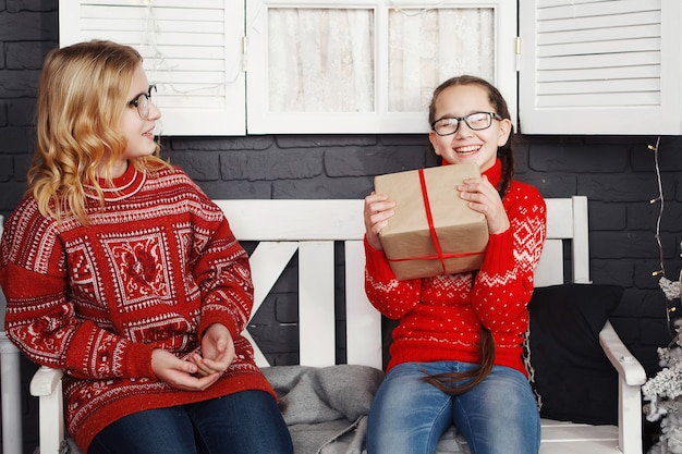 Teenage girls in a red christmas sweater give gift boxes while sitting on a bench.