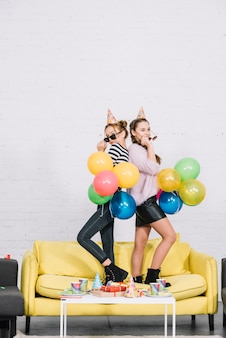 Teenage girls standing back to back holding balloons in hand on party