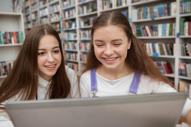 Девочки-подростки учатся вместе в библиотеке