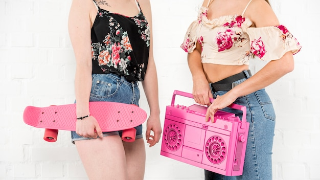 Teenage girls in summer clothes holding longboard and tape recorder