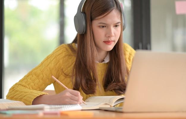 십대 소녀들은 헤드폰을 쓰고 온라인으로 공부하고 강의를 듣습니다.