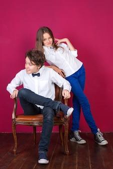 Девочки-подростки в джинсах и кроссовках позируют на раскрашенном розовом фоне стены в квартире-лофте ...