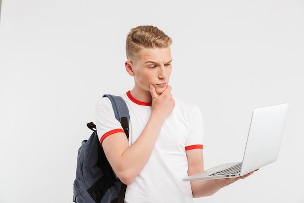Подросток 16-18 лет в футболке с рюкзаком держит открытый ноутбук и серьезно смотрит на экран, изолированный на белом