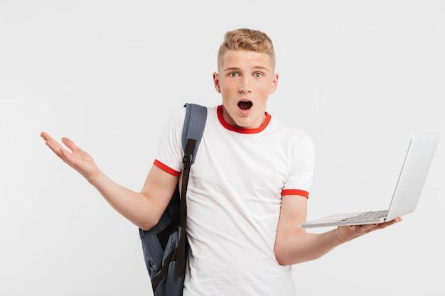 10代の男の開いているラップトップを保持し、白で隔離される困惑と腕を投げるバックパックとtシャツで16-18歳
