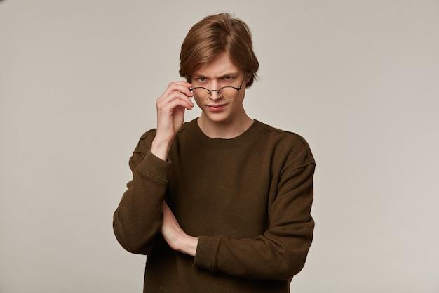 십 대 남자, 금발 머리를 가진 행복 찾는 남자. 갈색 스웨터와 안경을 착용.