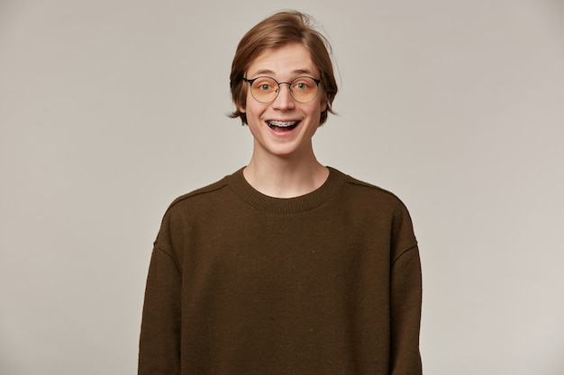 Teenage guy, happy looking man with blond hair. wearing brown sweater and glasses. has braces.