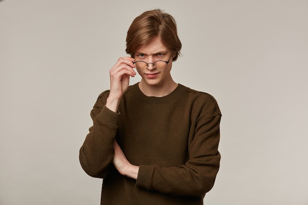Teenage guy, happy looking man with blond hair. wearing brown sweater and glasses.