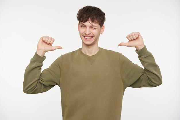 10代の男、ブルネットの髪、ピアスと剛毛を持つ幸せそうな男。カーキ色のセーターを着ています。親指で自分を指さします。白い壁の上に隔離されたウォッチングとウィンク