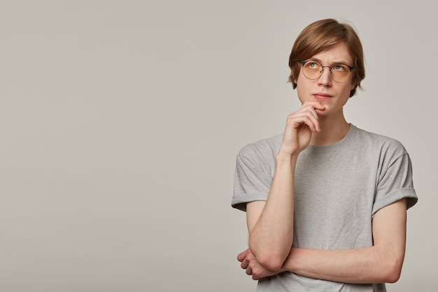 십 대 남자, 금발 머리를 가진 남자를 생각. 회색 티셔츠와 안경 착용. 사람들이 개념. 턱을 만지고 집중. 회색 벽 위에 고립 된 복사 공간에서 왼쪽을보고