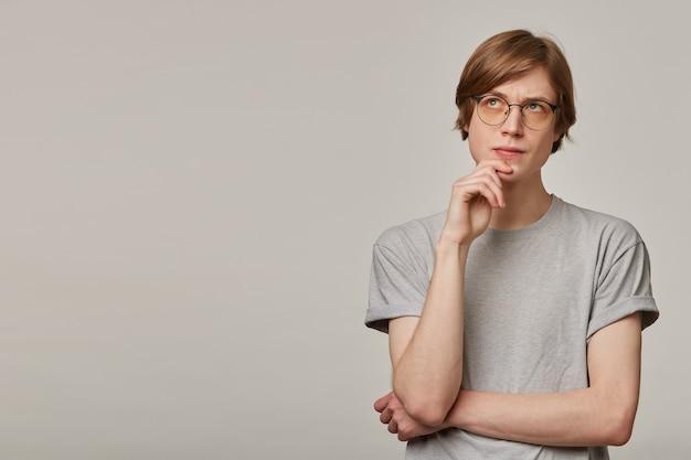 Ragazzo adolescente, uomo pensante con i capelli biondi. indossare t-shirt e occhiali grigi. concetto di persone. toccandosi il mento, concentrandosi. guardando a sinistra allo spazio della copia, isolato sopra il muro grigio