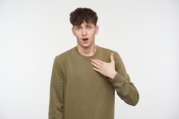Teenage guy, unhappy looking man with brunette hair, piercing and bristle. wearing khaki color sweater. pointing on himself with asking look. isolated over white wall