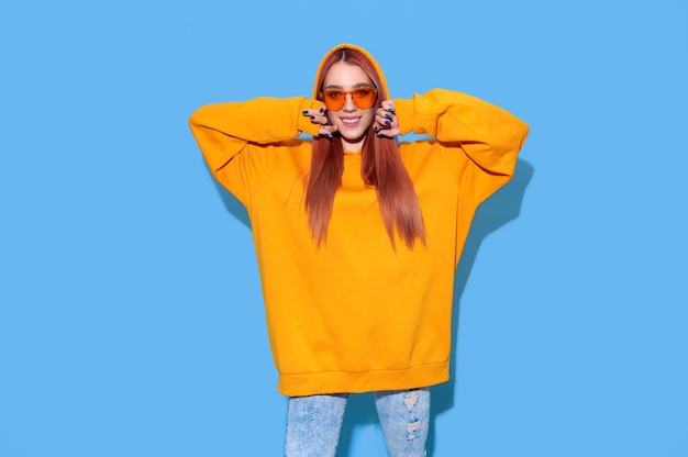 Teenage hipster girl in orange oversize hoodie and trendy sunglasses on bright blue background