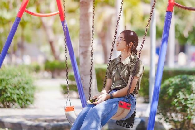 Подросток, слушающий музыку, сидя на качелях в парке.