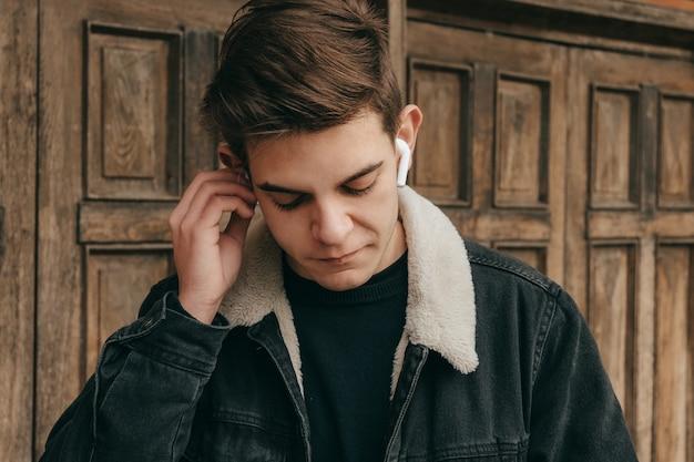 Teenage male listening to music with wireless headphones