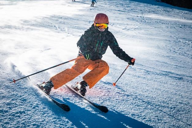 Подросток-лыжник поворачивает на склоне в солнечный день