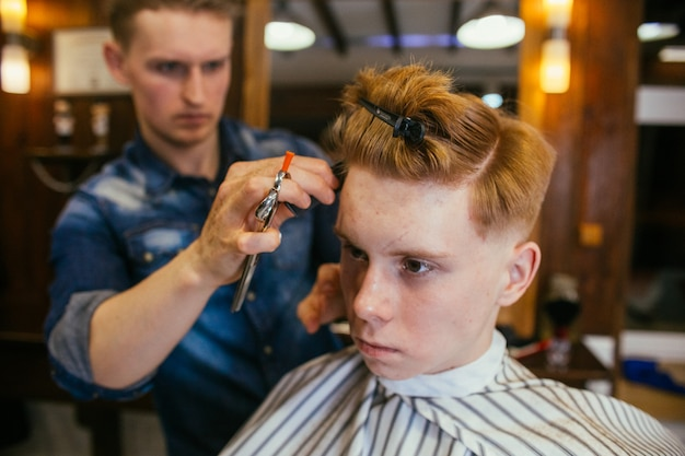 Teenage redhead boy haircuts hairdresser in the barber shop. fashionable stylish retro hairstyle