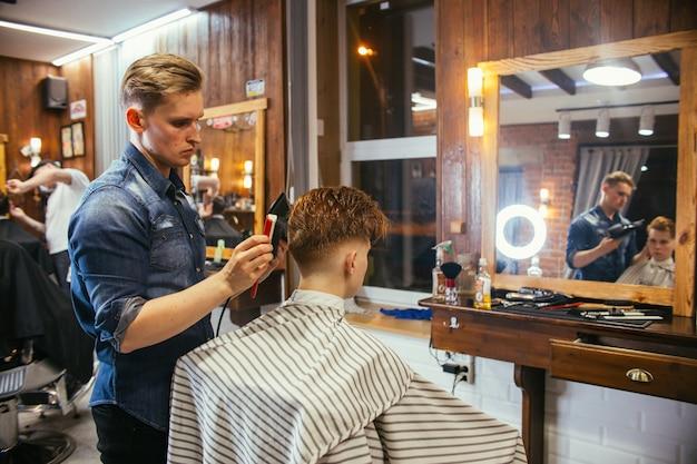 이발소에서 십대 빨간 머리 소년 이발 미용사. 세련된 세련된 복고풍 헤어스타일. 아름다운 머리를 한 아이의 초상화. 러시아, 스베르들로프스크, 2019년 2월 12일