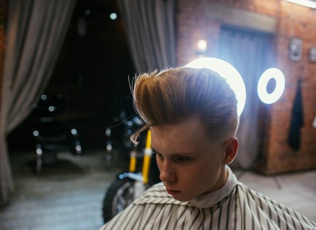 10代の赤毛の少年は理髪店で美容師を散髪します。ファッショナブルでスタイリッシュなレトロなヘアスタイル。美しい散髪の子供の肖像画。ロシア、スヴェルドロフスク、2019年2月12日