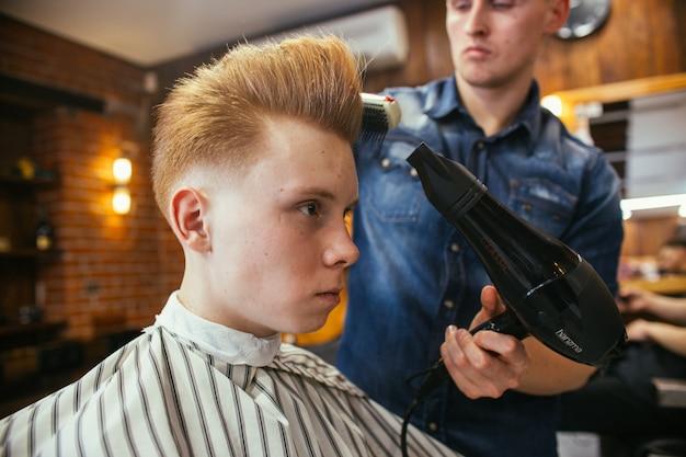 이발소에서 십 대 빨간 머리 소년 머리 미용사. 세련된 세련된 복고풍 헤어 스타일. 아름다운 머리를 가진 아이의 초상화입니다.