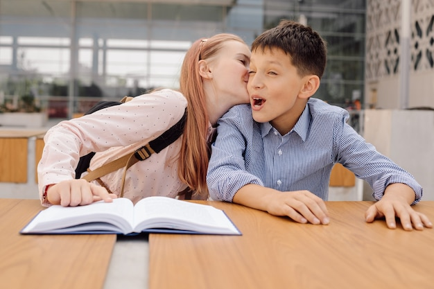 Teenage schoolgirl girl is whispering something in boy's ear or kissing him. first love