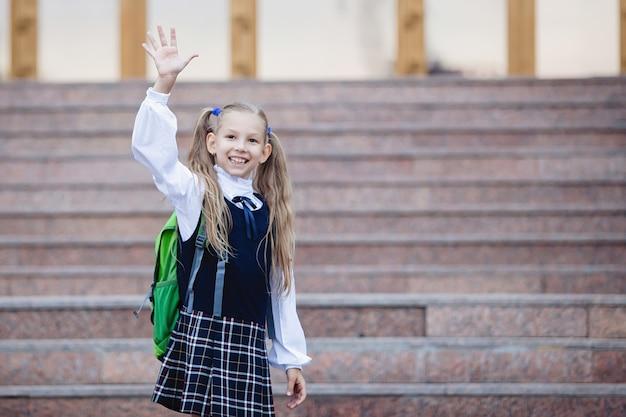 Школьница-подросток в форме с косичками, с рюкзаком в клетчатой юбке машет рукой на лестнице у входа в школу.