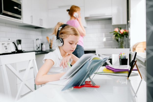 A teenage schoolgirl wears an online learning conference calling headset with a remote tutor from home. mom talking on the phone, teenage student using laptop, talking video chat in webcam, teaching l