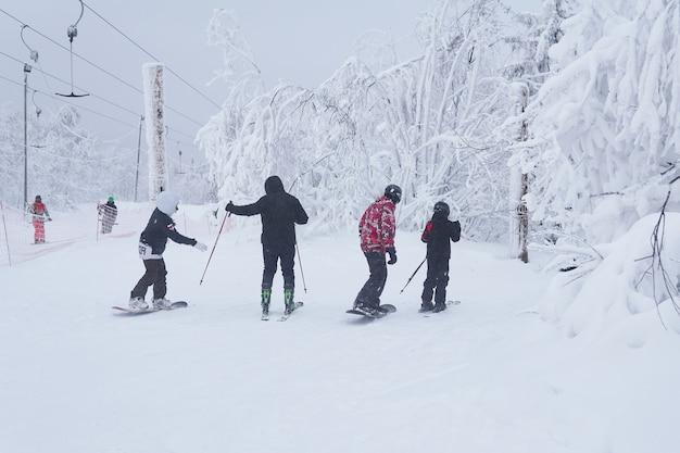 10代のスキーヤーとスノーボーダーが森の小道に沿って山を滑り降りようとしています