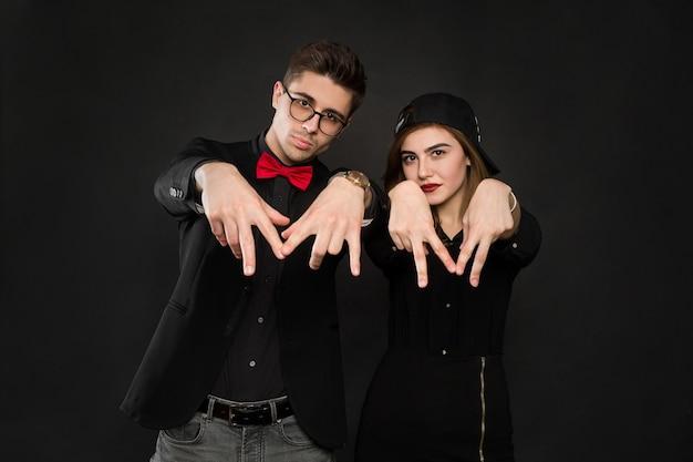 Подростковая улыбающаяся рэп-пара в черной одежде и черной кепке. изолированные на черном фоне.