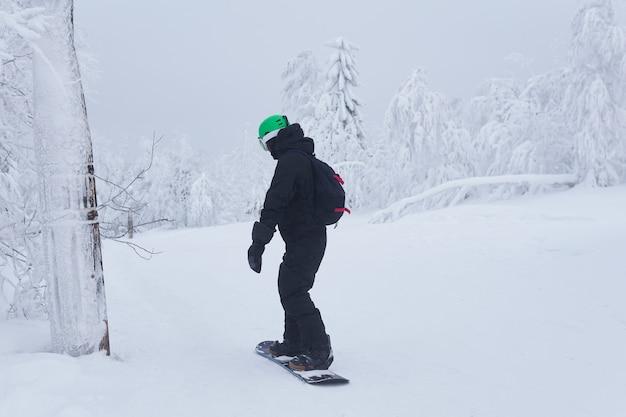凍るような天気で森の小道に沿って山の斜面を滑り降りる10代のスノーボーダー
