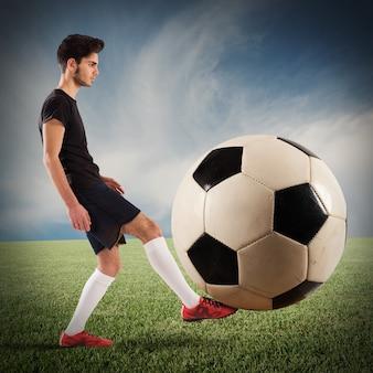 10 대 축구 선수가 큰 soccerball으로 재생