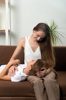 Сын-подросток положил голову на колени матери. материнская любовь. вертикальная рама.