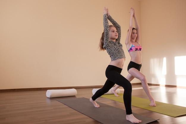 10代のスポーツ。子供のためのヨガ。禅の生活、スタジオでの女の子のためのストレッチ体操。フリースペース、健康的なライフスタイル、asanaコンセプトのジムの背景