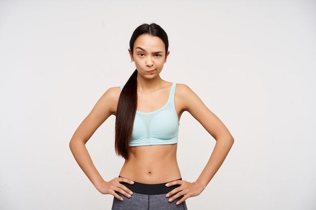 10代のスポーティな女の子、暗い長い髪の疑わしい探しているアジアの女性。スポーツウェアを着用し、腰に手をつないでください。眉を持ち上げて、白い背景の上に分離された状態でカメラを見て