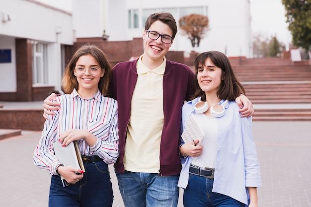 Teenage student boy embracing girl classmates and looking at camera