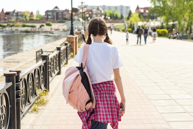 Подростковая студент девушка прогуливается по улице с рюкзаком. снова в школу, вид сзади