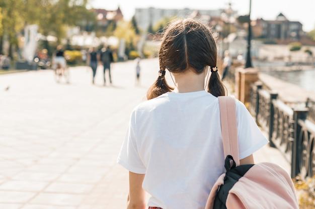 バックパックで通りを歩いて10代の学生の女の子