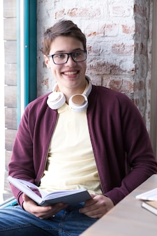 Teenage student in glasses and sitting at table and reading book