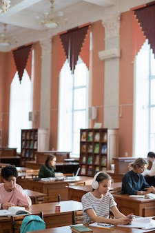 Студент-подросток просматривает смартфон за столом в библиотеке колледжа среди других учащихся, готовящихся к семинару