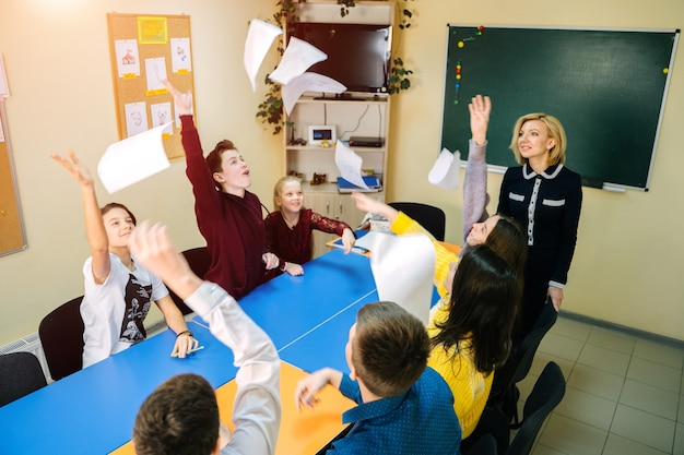Teenage student throughing papers in air. sitting at tables in class. teacher in front of class. happy children in school.