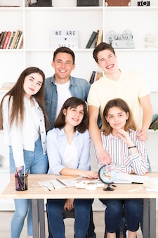 Teenage students gathered at table in classroom