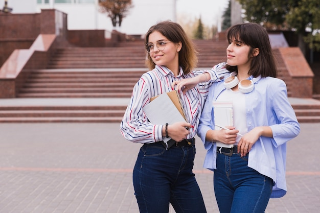 Teenage students in light shirts standing with books