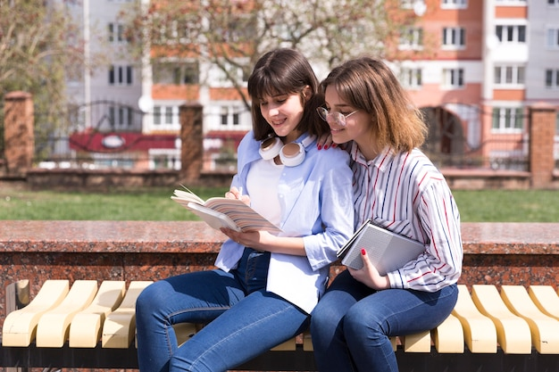 Teenage students sitting on bench with open books